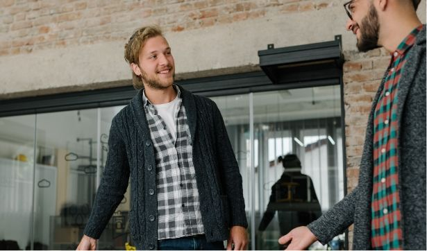 Two men that are wearing flannels smile at each other.